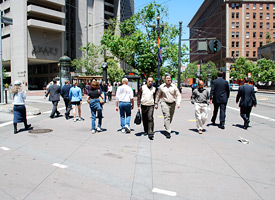 pedestrians crossing at busy intersection on Market Street