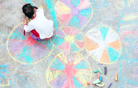 young child making chalk drawings