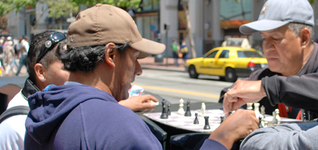 two men playing chess on sidewalk