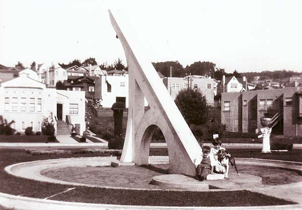 children sitting in front of large sun dial circa 1926