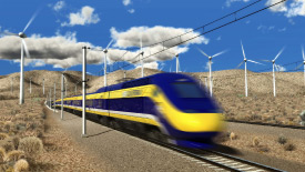 High speed train travelling past large wind turbines